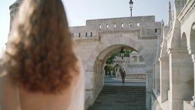 Una mujer joven o una novia muy hermosa en un vestido blanco, permanece el balcón del castillo viejo, y miradas en cómo el novio almacen de metraje de vídeo