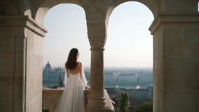 Una mujer joven o una novia muy hermosa en un vestido blanco, permanece el balcón del castillo viejo, y miradas en la ciudad almacen de metraje de vídeo