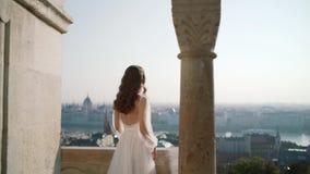 Una mujer joven o una novia muy hermosa en un vestido blanco, se acerca al balcón del castillo viejo, y a miradas en la ciudad metrajes