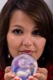 Una mujer joven ofrece una bola cristalina Imagenes de archivo