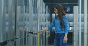 Una mujer joven para abrir la puerta del refrigerador para almacenar dispositivos y para comparar con otros modelos para comprar  metrajes