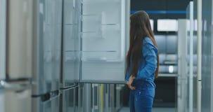 Una mujer joven para abrir la puerta del refrigerador para almacenar dispositivos y para comparar con otros modelos para comprar  almacen de video