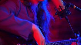 Una mujer joven pasa a través de las secuencias de la guitarra y de cantar una canción en la iluminación de neón