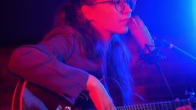 Una mujer joven pasa a través de las secuencias de la guitarra y de cantar una canción romántica en la iluminación de neón almacen de video
