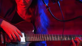 Una mujer joven pasa a través de las secuencias de la guitarra y del canto en la iluminación de neón