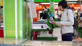 Una mujer joven pesa verduras en las escalas electrónicas en tienda almacen de video