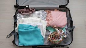 Una mujer joven pone cosas en una maleta metrajes