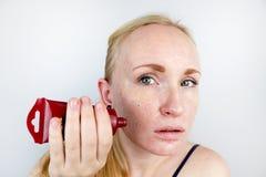 Una mujer joven pone una máscara del gel en su cara Cuidado para aceitoso, piel del problema foto de archivo