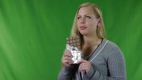 Una mujer joven a probar la barra de chocolate metrajes