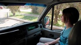 Una mujer joven, profesional médico, viaja en ambulancia al paciente almacen de video