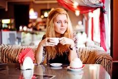 Una mujer joven que almuerza en una risa del café Foto de archivo libre de regalías