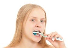 Una mujer joven que aplica sus dientes con brocha Imagenes de archivo