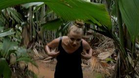 Una mujer joven que camina a través de una selva tropical metrajes