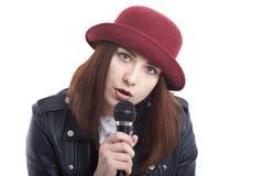 Una mujer joven que canta con un micrófono que lleva una camiseta blanca Fotos de archivo libres de regalías