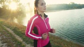 Una mujer joven que corre en el lago en la salida del sol metrajes