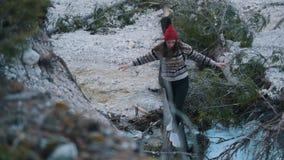Una mujer joven que cruza el río rocoso en el registro con la guitarra almacen de video