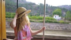 Una mujer joven que disfruta de viajar en un tren viejo, admirando ubicaciones turísticas hermosas almacen de video