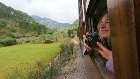 Una mujer joven que disfruta de viajar en un tren viejo almacen de video