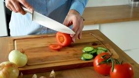 Una mujer joven que es de cocinar y que corta los tomates frescos para la ensalada en tabla de cortar almacen de metraje de vídeo
