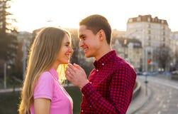 Una mujer joven que habla con un hombre y que se ríe del CCB del paisaje urbano Imágenes de archivo libres de regalías