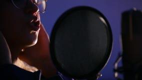 Una mujer joven que hace una pausa el mic y que registra una canción en el estudio