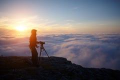 Una mujer joven que hace una película en las montañas brumosas en la puesta del sol fotografía de archivo libre de regalías