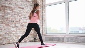 Una mujer joven que hace sentar-UPS en un pie en una estera de la yoga en un club de fitness almacen de video