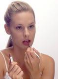 Una mujer joven que hace su maquillaje Fotos de archivo