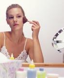Una mujer joven que hace su maquillaje Fotos de archivo libres de regalías