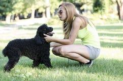 Una mujer joven que juega con su perro fotos de archivo