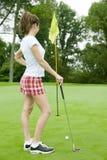 Una mujer joven que juega a golf Fotografía de archivo