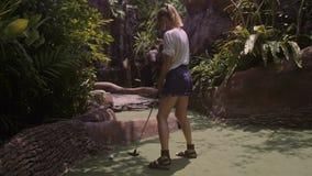 Una mujer joven que juega a mini golf almacen de video