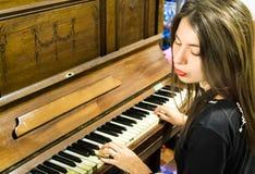 Una mujer joven que juega un piano viejo del vintage con los ojos cerrados Fotografía de archivo libre de regalías