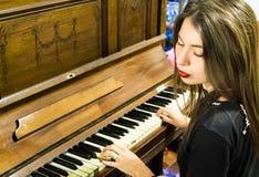 Una mujer joven que juega un piano viejo del vintage con los ojos cerrados Imágenes de archivo libres de regalías
