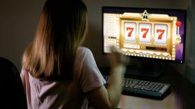 Una mujer joven que jugaba en un casino en línea ha ganado un bote La morenita presiona en el teclado y espera suerte almacen de metraje de vídeo