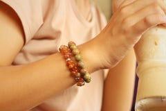 Una mujer joven que lleva una pulsera colorida Fotografía de archivo libre de regalías