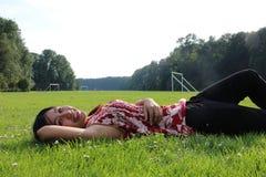 Una mujer joven que miente en un campo de hierba Foto de archivo libre de regalías