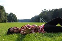 Una mujer joven que miente en un campo de hierba Imagen de archivo libre de regalías