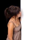 Una mujer joven que mira a escondidas detrás de la pared Imagen de archivo