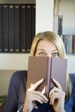 Una mujer joven que mira furtivamente Foto de archivo libre de regalías