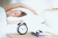 Una mujer joven que pone su despertador apagado en la mañana imágenes de archivo libres de regalías