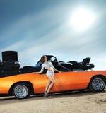 Una mujer joven que presenta cerca de un coche retro anaranjado imagen de archivo