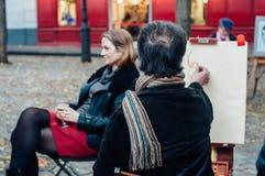 Una mujer joven que presenta para servir al artista de la calle Imagen de archivo libre de regalías