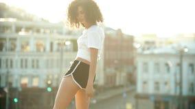 Una mujer joven que realiza el baile atractivo en el tejado - mira sobre su hombro - puesta del sol almacen de video