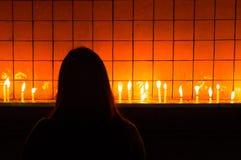 Una mujer joven que ruega y que enciende una vela Imagen de archivo libre de regalías