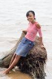 Una mujer joven que se inclina contra un árbol de coco Imagen de archivo libre de regalías