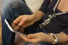 Una mujer joven que se sienta en el sofá para descansar con un smartphone adentro Fotos de archivo