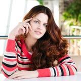 Una mujer joven que se sienta en un café Fotografía de archivo libre de regalías