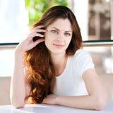 Una mujer joven que se sienta en un café Imágenes de archivo libres de regalías