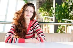 Una mujer joven que se sienta en un café Imagen de archivo libre de regalías